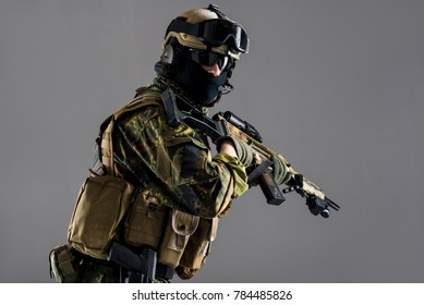 Portrait of serious man in helmet and balaclava keeping weapon in hands. He looking at camera. Armor concept. Isolated