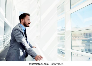 Portrait of a serious man office worker dressed in elegant clothes watching in window while standing in modern office space, thoughtful young male entrepreneur in suit resting after business meeting
