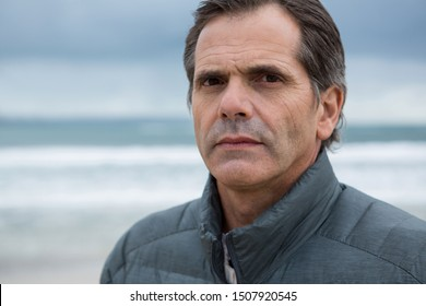 Portrait of serious man on beach during winter