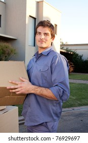 Portrait of a serious man outdoors with cardboard moving boxes