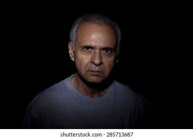 Portrait of serious man over black background