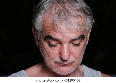 Portrait of serious mature man in studio on black background. Unretouched photography