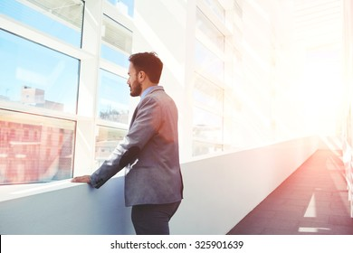 Portrait of serious men boss dressed in luxury elegant clothes watching in window while standing in modern space, thoughtful young successful male entrepreneur in suit resting after business meeting