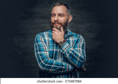 Portrait of serious middle age bearded male dressed in plaid flannel shirt over grey background.