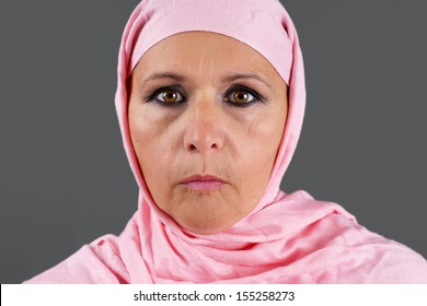 Portrait of serious middle aged muslim woman with pink scarf or hijab