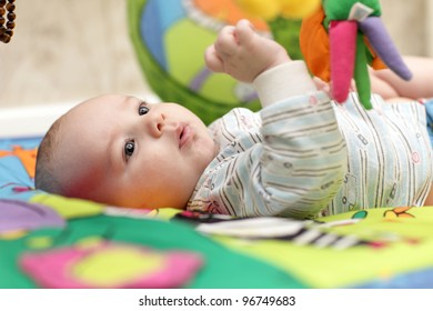 Portrait of serious playing baby boy at home