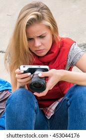 Portrait of serious and puzzled girl using camera outdoor