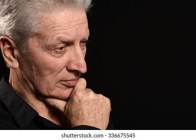 Portrait of a serious senior man on black background