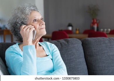 Portrait of serious senior woman answering call at home. Grandma sitting on couch ant talking on cellphone. Elderly people and communication concept