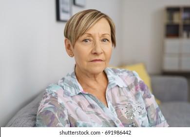 Portrait of serious senior woman sitting on sofa