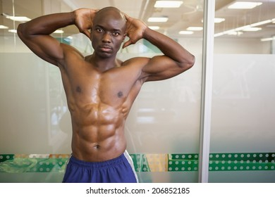 Portrait of a serious shirtless muscular man posing in gym