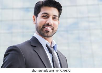 Porträt eines ernsten lächelnden glücklichen arabischen Geschäftsmanns oder Arbeiter in schwarzem Anzug mit Krawatte und Hemd mit Bart steht vor einem Bürogebäude.