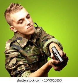 portrait of a serious soldier aiming against a green background