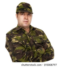 portrait of a serious soldier standing against a white background