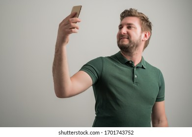 Portrait of serious stylish attractive man with thick beard, dressed in casual green t shirt taking selfie photo isolated on gray background with copy space advertising area