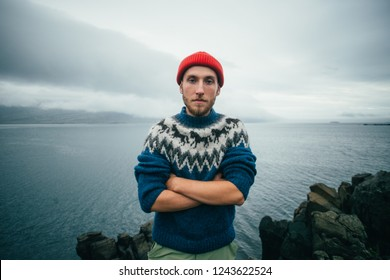 Portrait of serious and tough young bearded man in traditional authentic blue wool sweater with ornaments and red sailor or fisherman beanie stand with crossed arms and look at camera at sealine.
