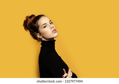 Portrait of serious woman looking at camera while posing in studio on yellow background. Girl wearing warm pullover and nice round shaped earrings. Fashion and lifestyle concept