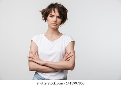 Portrait of serious woman with short brown hair in basic t-shirt frowning and looking at camera isolated over white background
