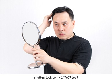 Portrait of serious young Asian bald man with alopecia, checking hairline while looking at the mirror isolated on white background. Hair loss, hair transplant concept.
