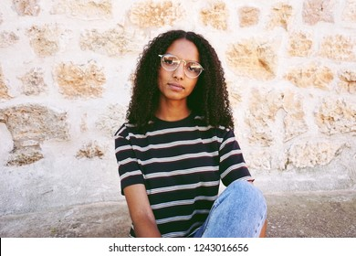A portrait of serious young black woman wearing glasses, jeans and a striped t-shirt , sitting on the ground and curly hair