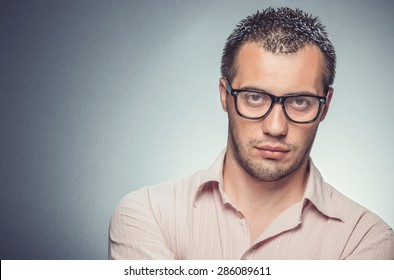 Portrait of a serious young businessman over gray dark background. Man with eyewear looking, studio shot
