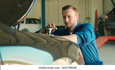 Portrait of serious young caucasian auto mechanic man using nut socket wrench for nuting of the screwed under the hood of car. Indoor.