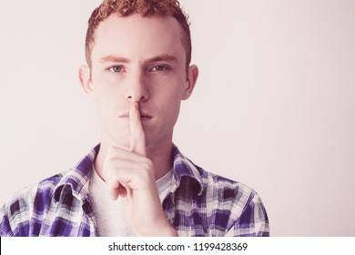 Portrait of serious young Caucasian redhead man wearing checked shirt standing with finger on lips showing silence gesture. Secrecy concept