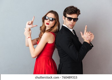 Portrait of a serious young couple dressed in formal wear and sunglasses standing back to back and showing gun gesture over gray wall background