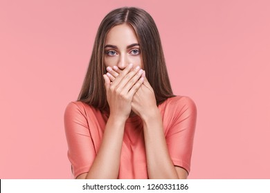 Portrait of serious young european woman covering mouth with both hands keeping a secret. Freckled redhead female in blouse doesn't want to spread rumors or some confidential information