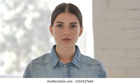 Portrait of Serious Young Girl Looking at Camera