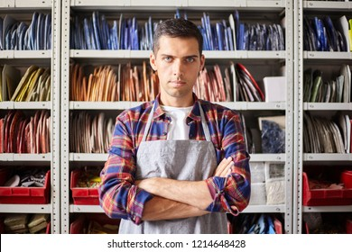 Portrait of serious young man in apron standing with arms crossed and looking at camera in workshop