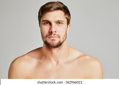 Portrait of a serious young man with bare shoulders on a gray background, powerful swimmers shoulders, beard, charismatic, adult, brutal, athletic, edited photo