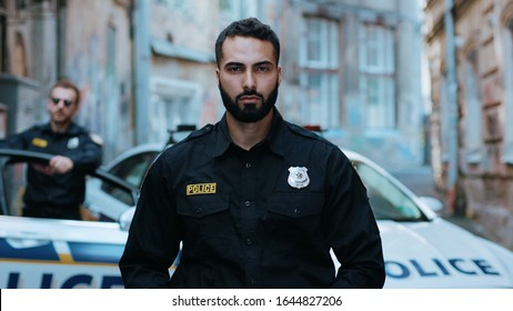Portrait serious young man cops hold pistol stand near patrol car look at camera enforcement officer police uniform auto safety security communication control policeman portrait close up slow motion