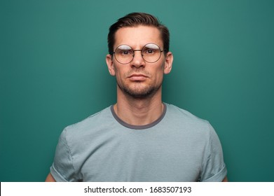 Portrait of a serious young man in glasses on a green background