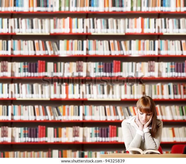 Portrait d'un jeune étudiant sérieux lisant un livre dans une bibliothèque