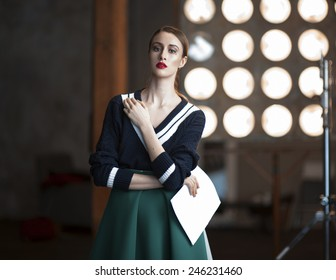 Portrait of a serious  young woman standing backstage with her scripts wearing black sweater and green skirt