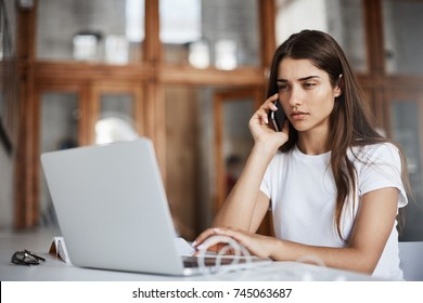 Portrait of serious young woman talking to a customer on phone running her successful online business making cat videos.