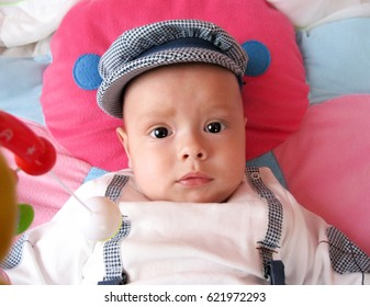 Portrait of seriously little child in cap, watching in the camera.