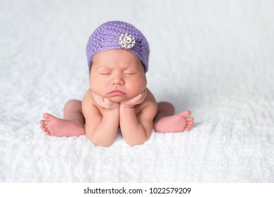 Portrait of a seven day old sleeping newborn baby girl. She is wearing a purple flapper hat with rhinestone button embellishment.