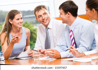 Portrait of several business people sitting in office and discussing new plans and ideas