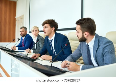 Portrait of several business people sitting in row participating in political debate during press conference answering media questions speaking to microphone