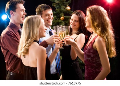 Portrait of several friends making a clink of bocals of champagne