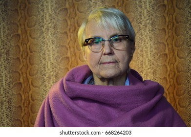 portrait of severe, formidable caucasian old woman. She is stylish grandmother with grey hair and white shirt, fashionable glasses, pink poncho or scarf. Background - snake print. Yellow light.