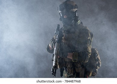 Portrait of severe peacemaker in helmet and balaclava keeping assault rifle in arms. Protection concept