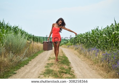 7a95f403989d1 Portrait of sexi tanned girl in red short dress carrying retro suicase  walking barefoot along earth