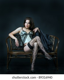 Portrait of sexual elegant brunette in underwear, sitting on a wicker couch  and covered with delicate silk