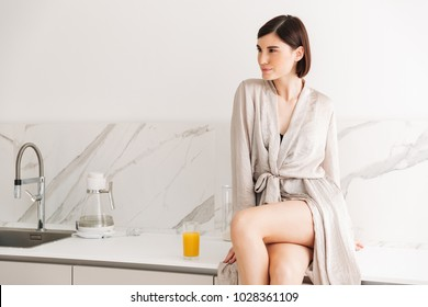 Portrait of sexual slim woman with short dark hair wearing robe sitting in kitchen, on table with crossed legs and drinking orange juice