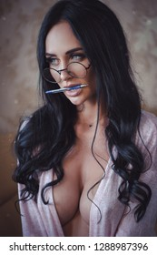 Portrait of sexual woman with pen and glasses indoors