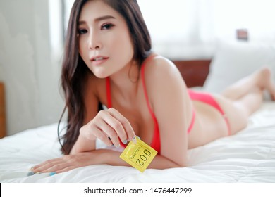 Portrait sexy asia woman lying on the bed with condom, safe sex concept