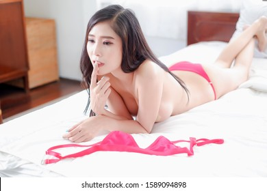 Portrait sexy asia woman wear red lingerie or underwear lying on the bed